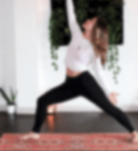 Blurred photo of yoga teacher doing the warrior pose